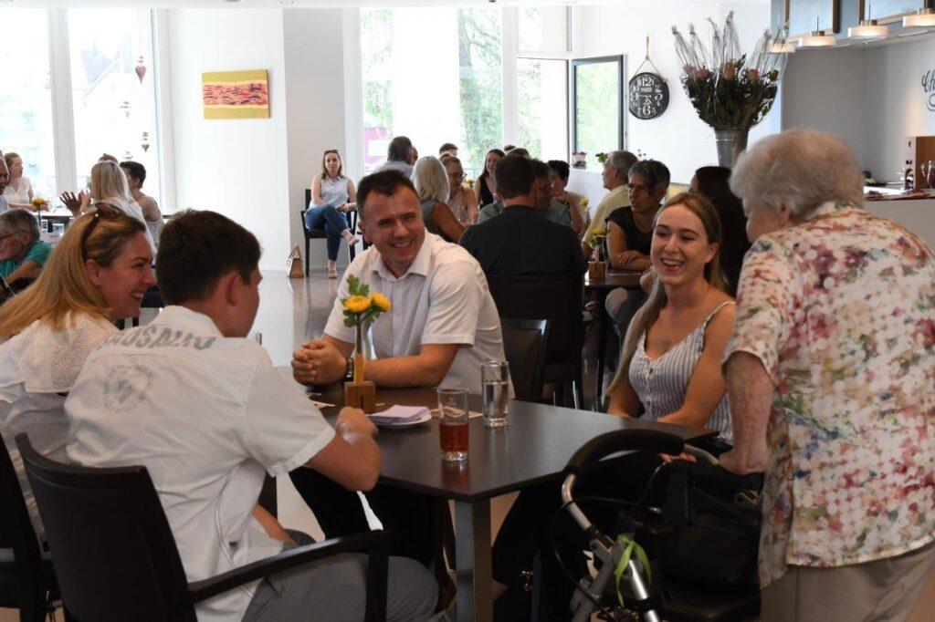 """Archivbild: Lachende Personen an Restauranttischen """"Chez Grand Maman"""" Sonnenhof."""